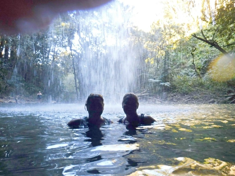 two women swimming under a waterfall