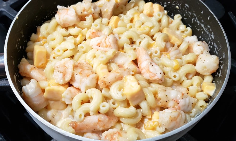 mac and cheese with shrimp mixed in a pan