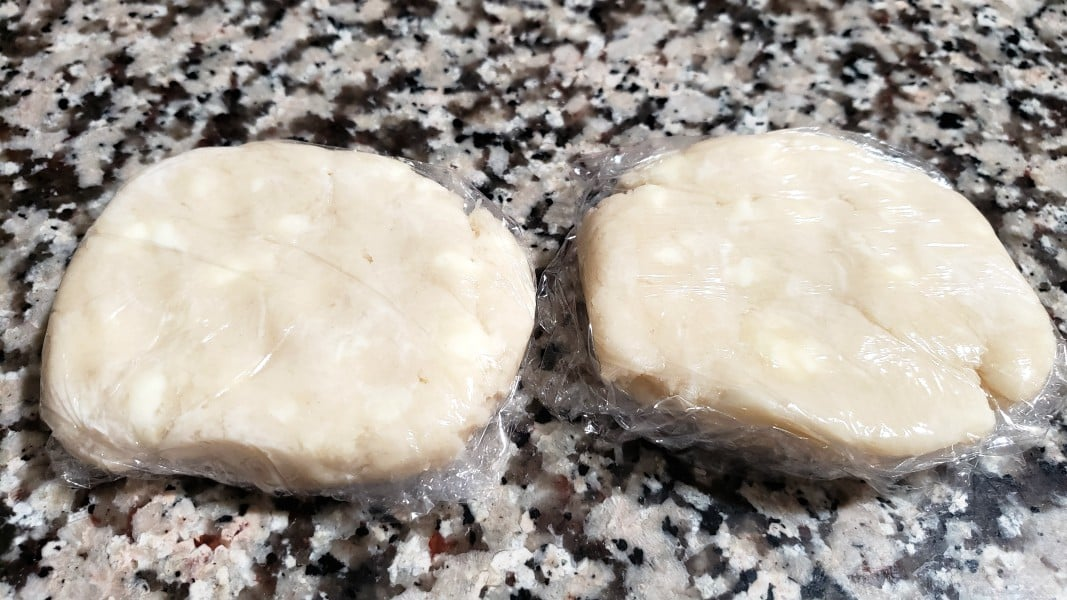 two pie dough discs wrapped with plastic wrap