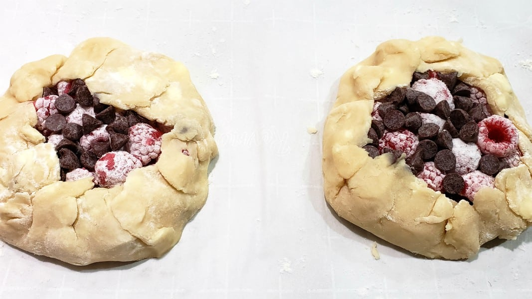 outer edges of pie dough folded up to make tart baskets around filling
