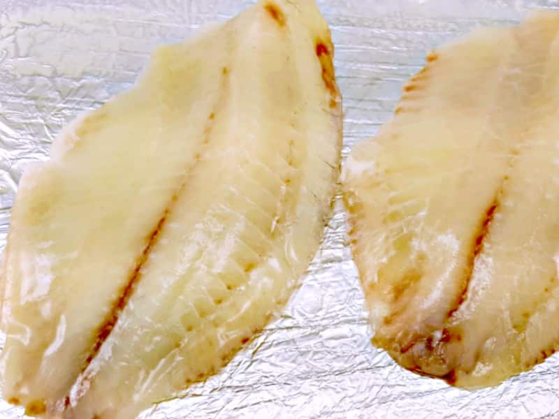 two tilapia filets on a tin foil lined baking sheet