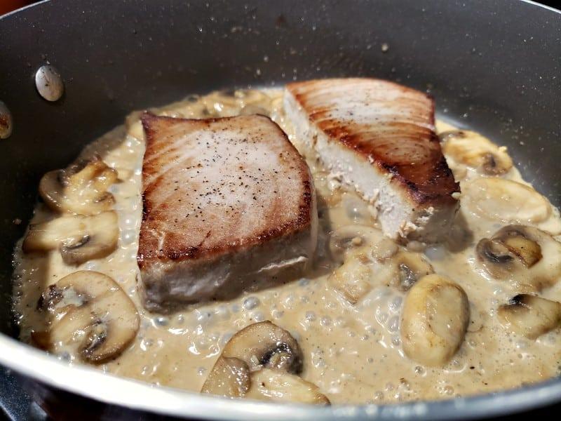tuna steaks cooking in a pan with creamy mushroom sauce