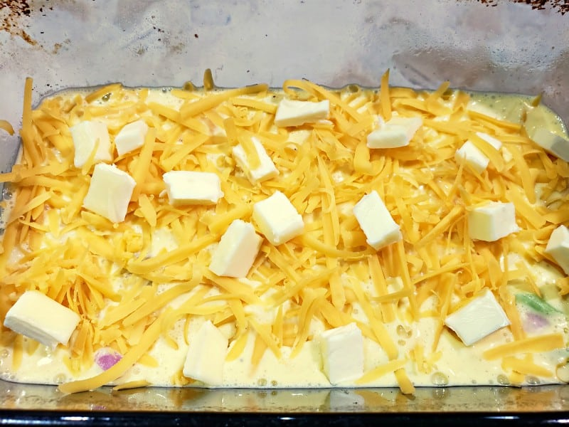 more cheese and pats of butter layered on top of quiche ingredients in a loaf pan