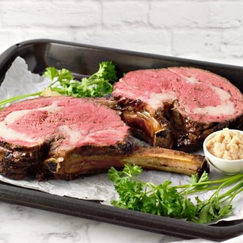 Two Prime Rib Roast steaks with a side of horseradish