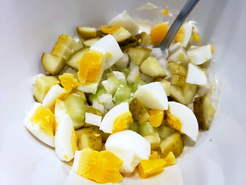 diced onion, celery, hardboiled egg, and pickles in a bowl