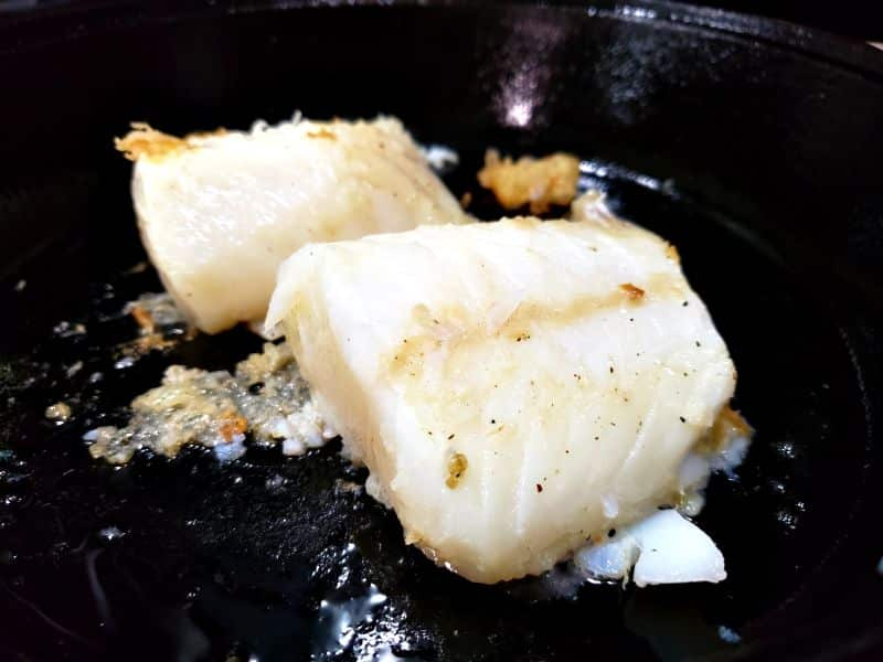2 cod filets cooking in a skillet