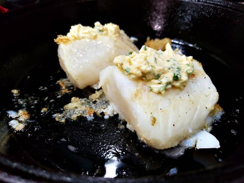 2 cod filets in a skillet topped with garlic butter