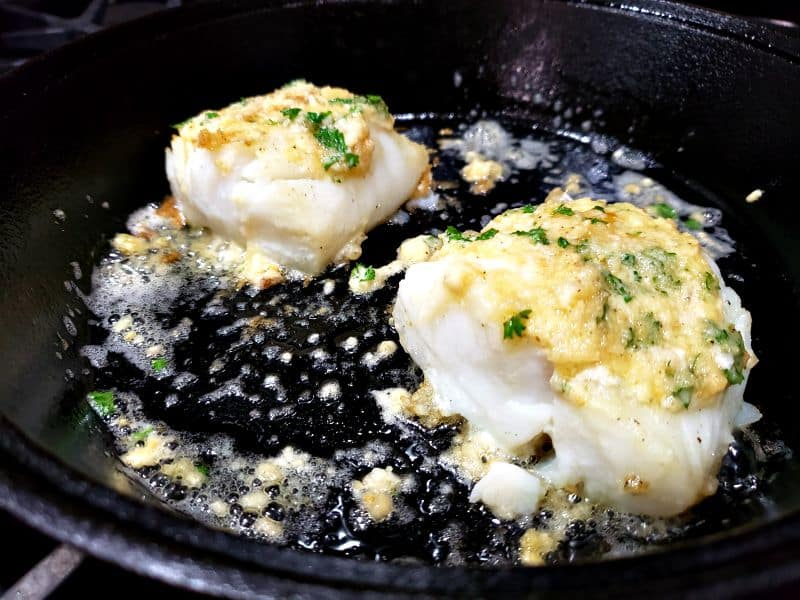 two cod filets cooking in a skillet with garlic butter