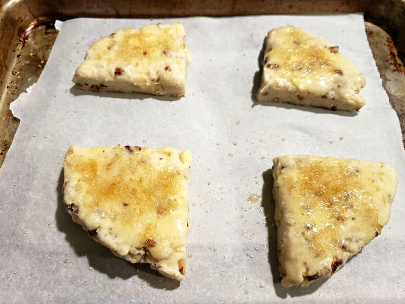 4 butter pecan scones on a baking tray topped with butter and sugar