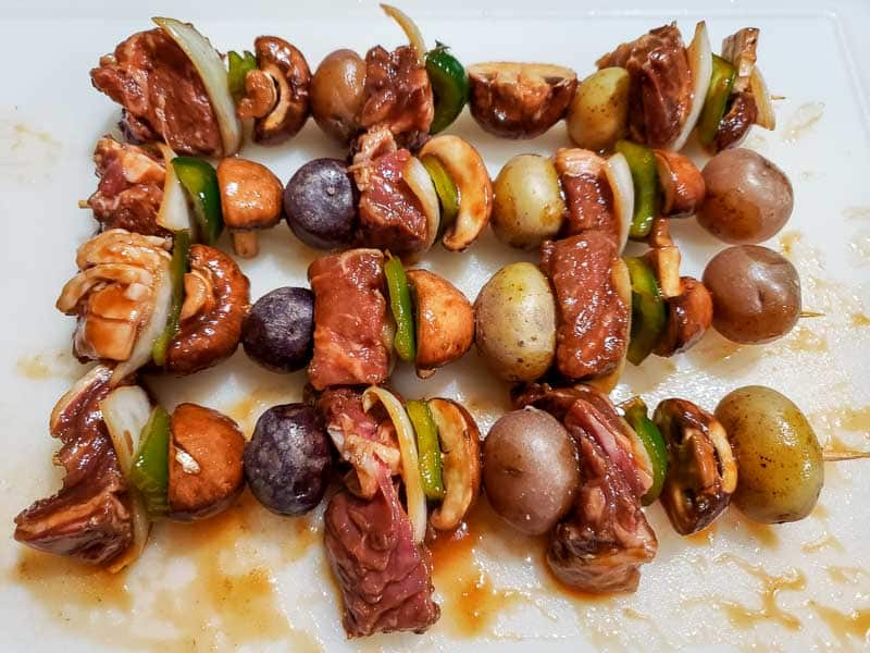 marinated ingredients added to the skewers ready to grill