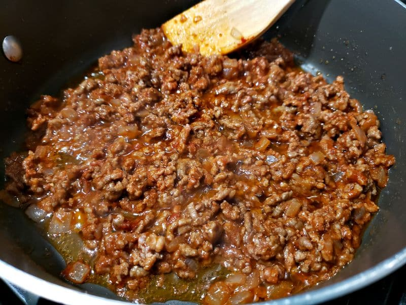 ground beef and tomato paste cooking in a pan