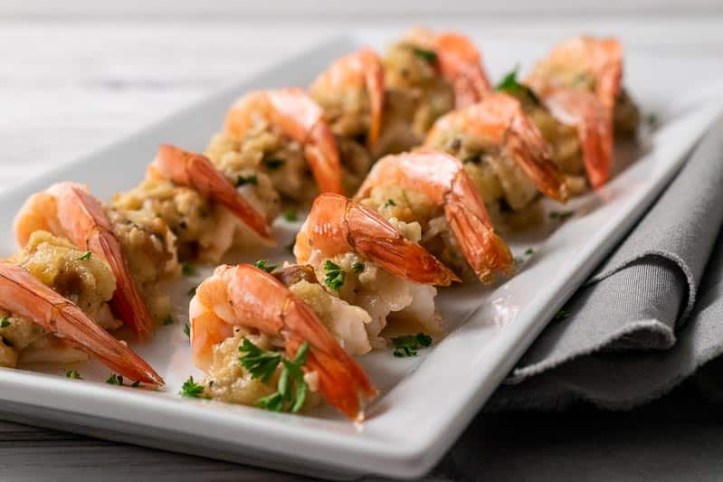 12 easy butterflied and baked stuffed shrimp on a platter