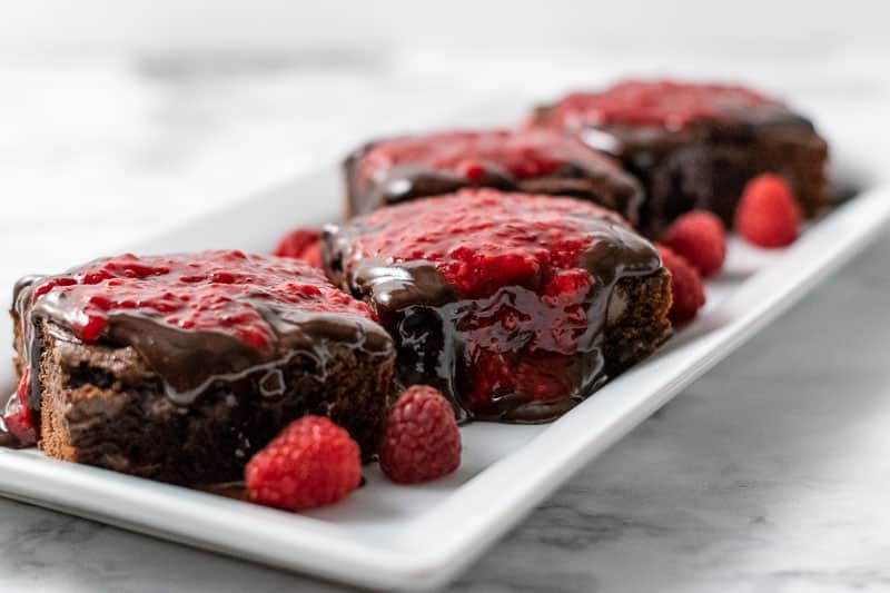 4 brownies with raspberry sauce and chocolate drizzle on a platter