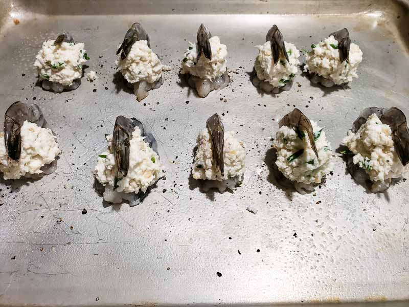 10 shrimp on a baking sheet stuffed with crab mixture