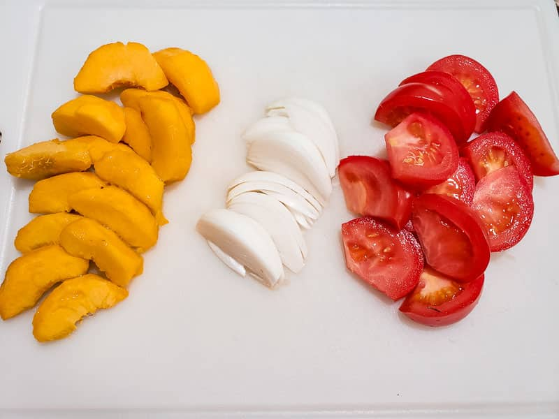 peaches, onions, and tomato wedges on a cutting board