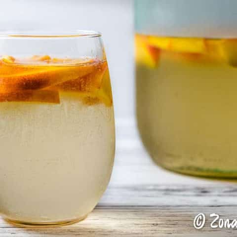 a glass and a pitcher of white peach sangria
