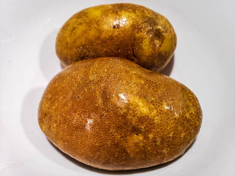two oiled potatoes in a bowl