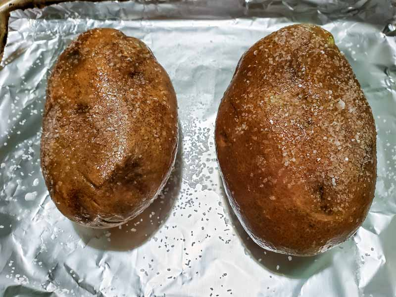 two oiled and salted potatoes on a baking sheet