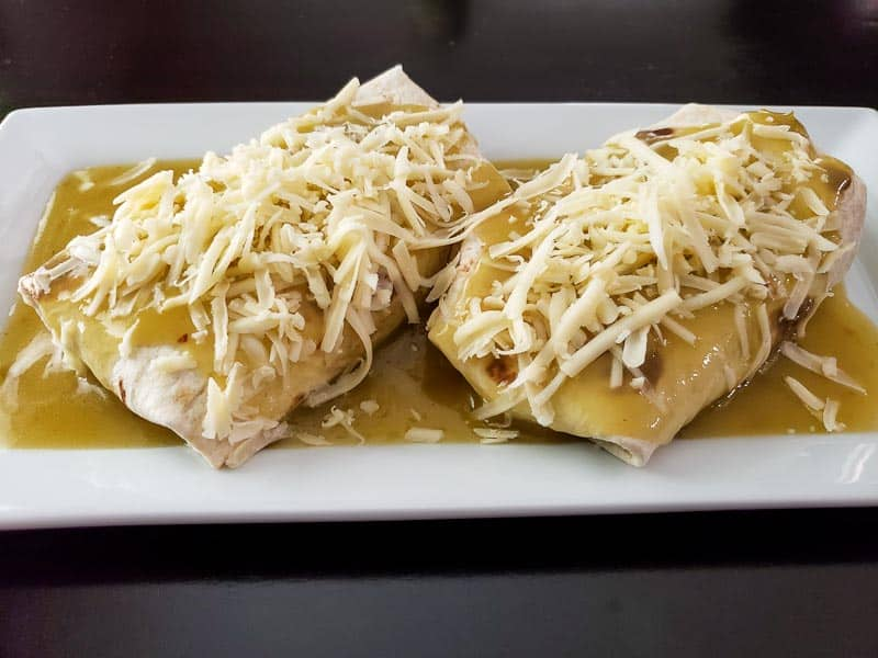 two burritos covered in green sauce and white shredded cheese on a platter