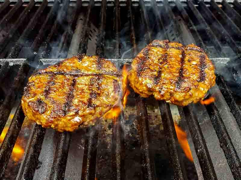 two taco burgers cooking on a grill