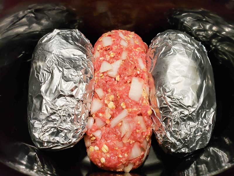 meatloaf and tin foil wrapped potatoes in a crockpot