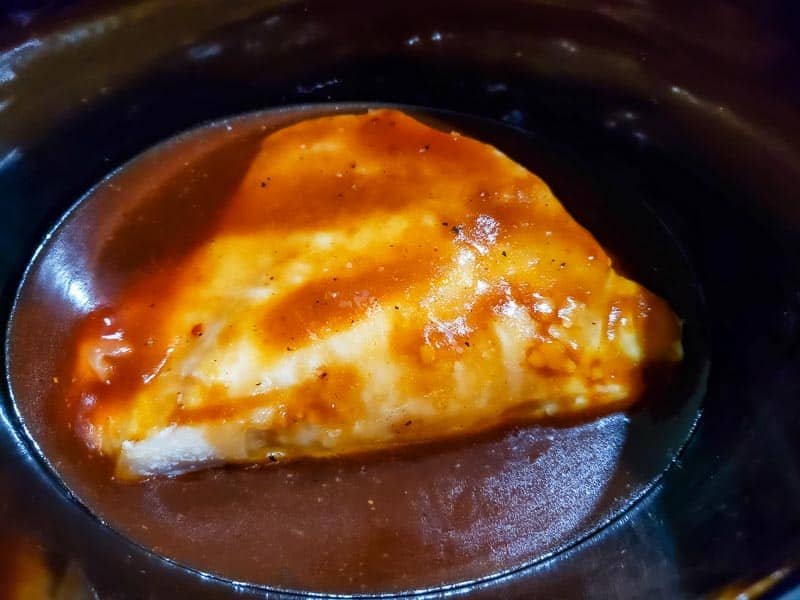 chicken breast covered in zesty bbq sauce in a crockpot