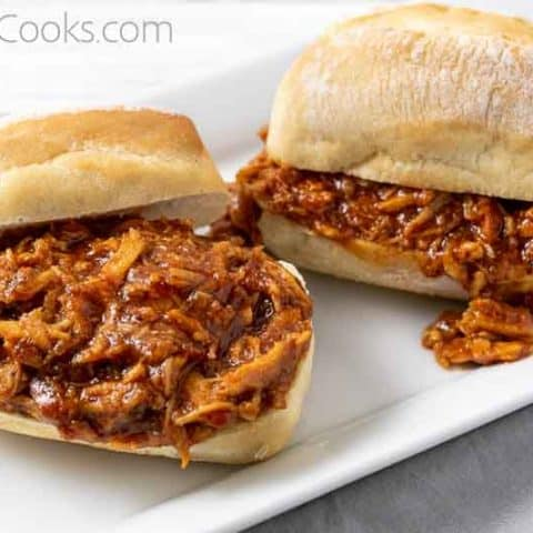 two sandwiches with zesty bbq shredded chicken on them