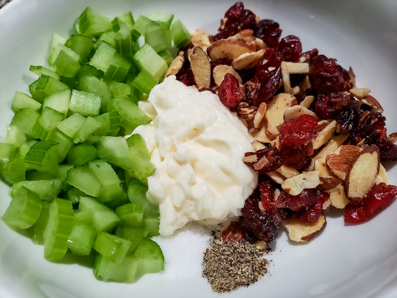 diced celery, mayo, dried cranberries, almonds, salt, and pepper in a bowl
