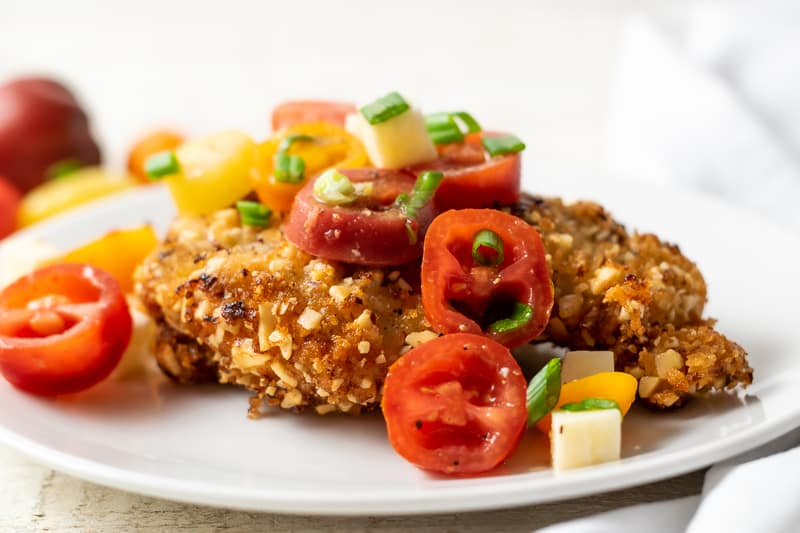 Almond Crusted Chicken and Italian Tomato Salad up close on a plate