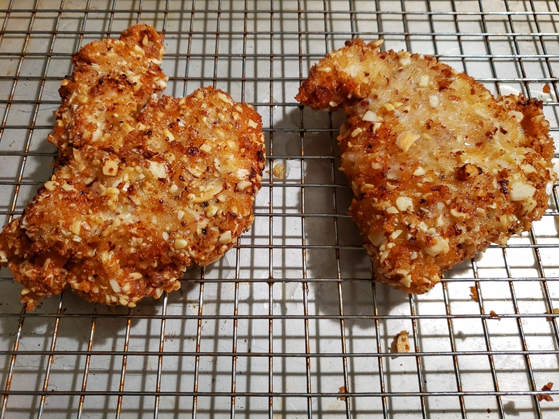 two cooked almond crusted chicken breasts draining on a rack