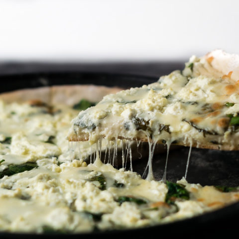 lifting out one slice of Goat Cheese and Spinach Pizza