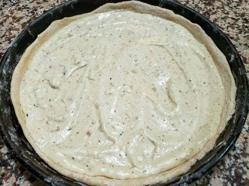 white garlic sauce spread over pizza dough