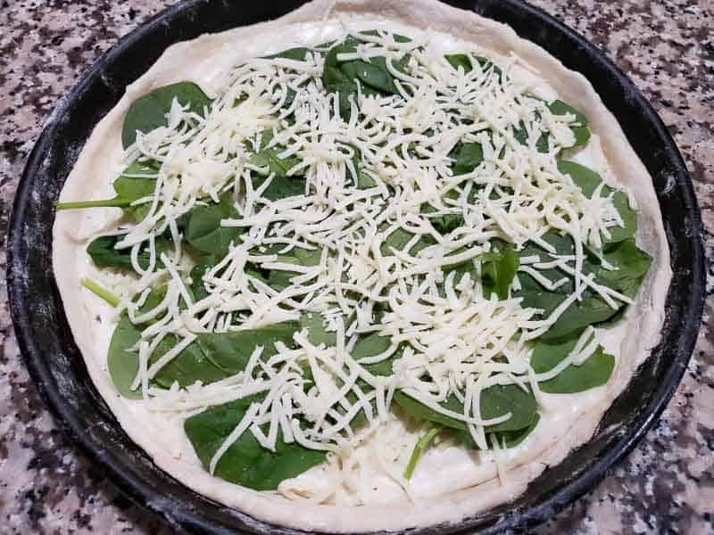 more mozzarella layered on pizza