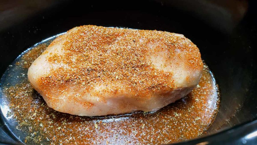 a boneless chicken cutlet in a crockpot sprinkled with taco seasoning