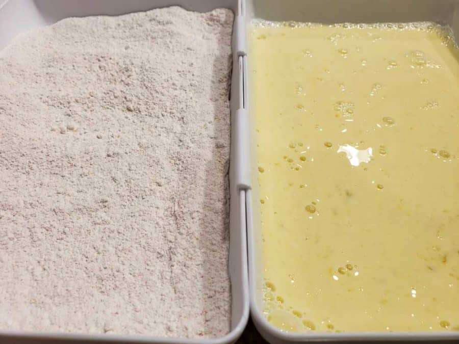 flour and seasoning mixture in tray on left and egg, milk, and vinegar mixture in tray on right