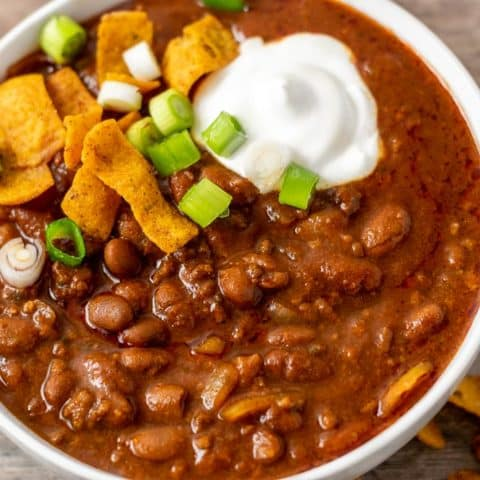 a bowl of chili topped with sour cream, green onion, and fritos
