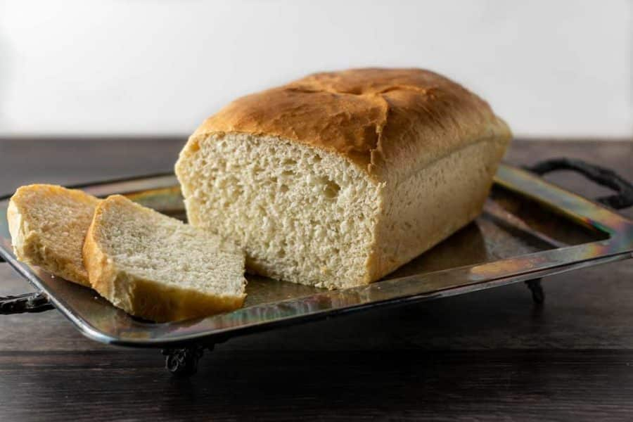 a loaf of bread with two end slices cut on a tray