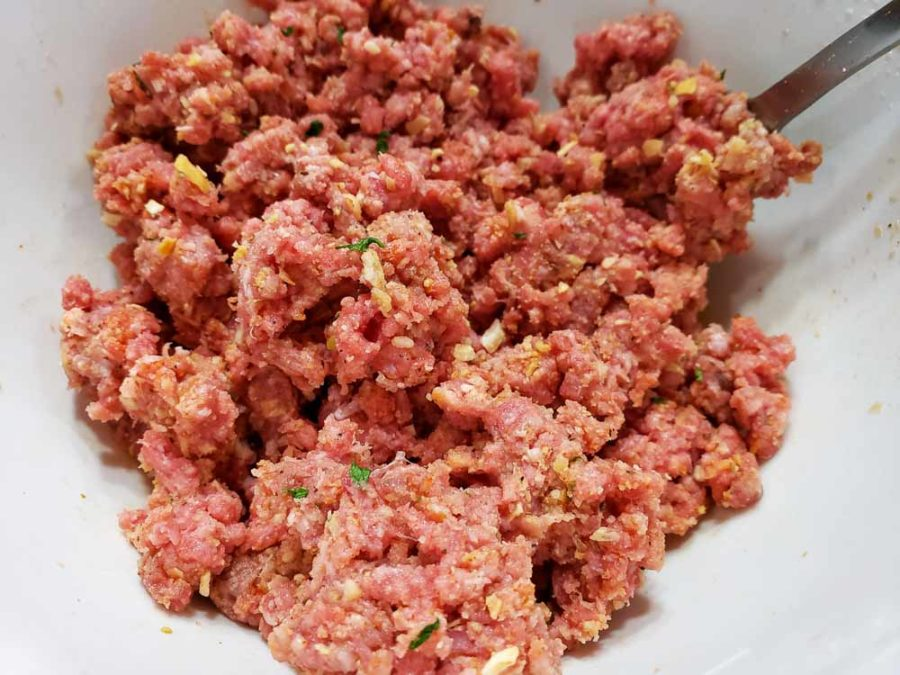 ground beef, onion flakes, onion powder, parsley, celery seed, paprika, black pepper, bread crumbs, and milk mixed together in a bowl