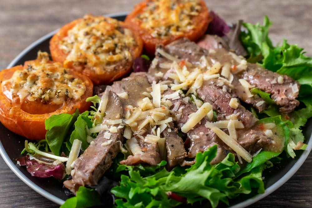 salad greens topped with steak, parmesan cheese, and dressing with 3 parm broiled tomatoes