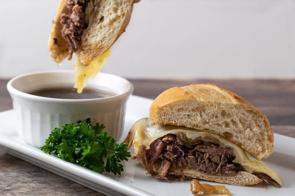 Crockpot French Dip Sandwich dipping into Au Jus