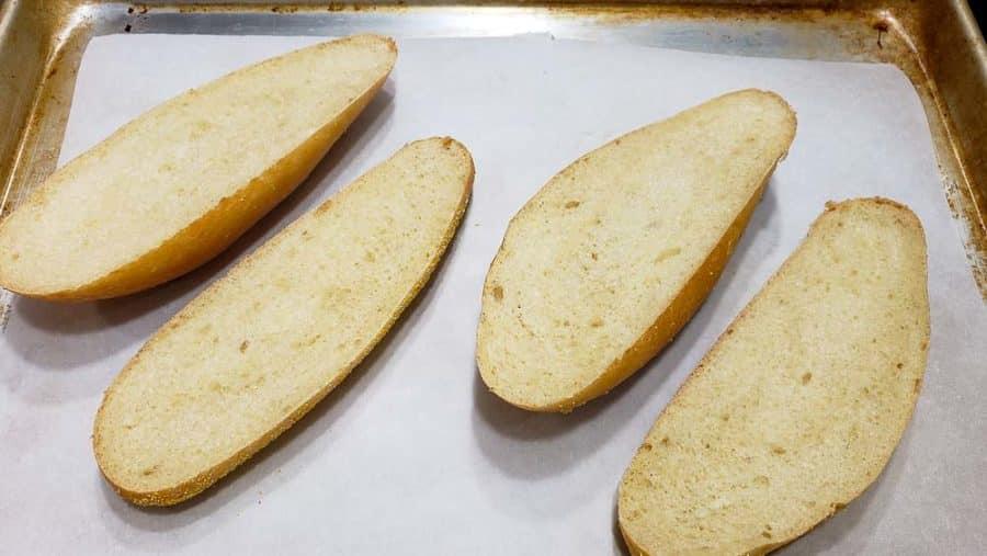 two hoagie sandwich rolls split on a baking sheet