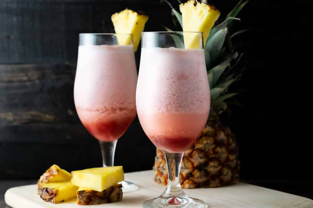 2 Hawaiian Lava Flow drinks with pineapple garnish