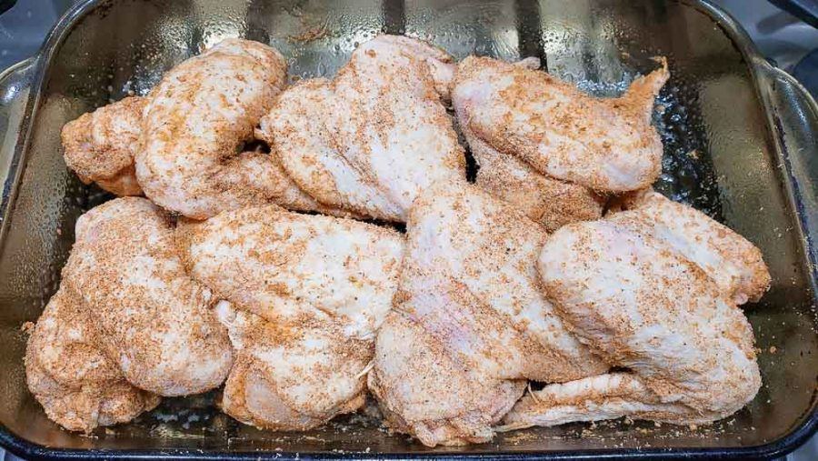raw chicken wings sprinkled with seasonings in a baking dish