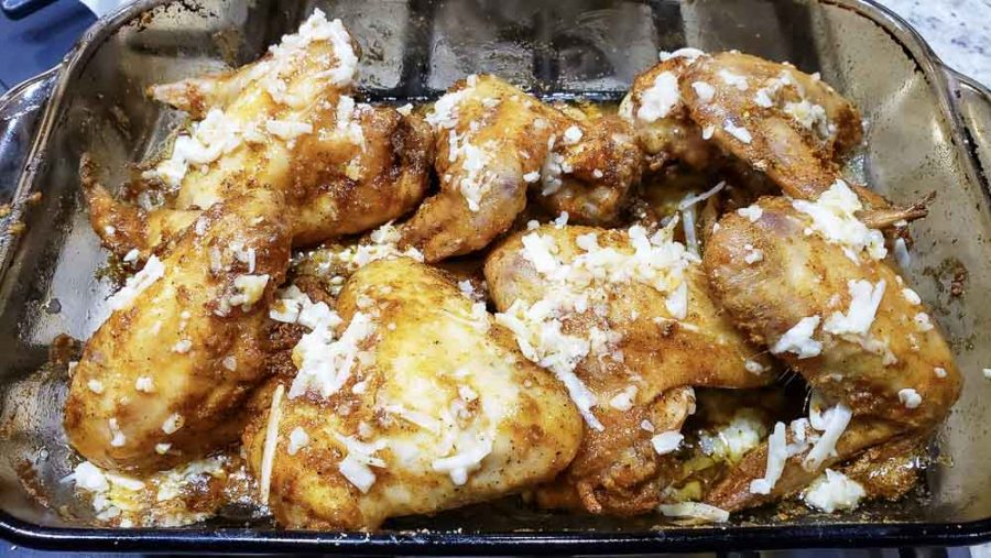 half baked chicken wings covered in butter, garlic, and parm sauce in a baking dish