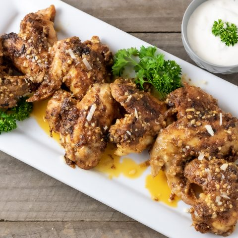 close up of garlic parm chicken wings on a platter with a side of ranch dressing
