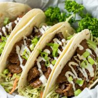 a graphic with 4 Korean BBQ Tacos in a paper lined basket