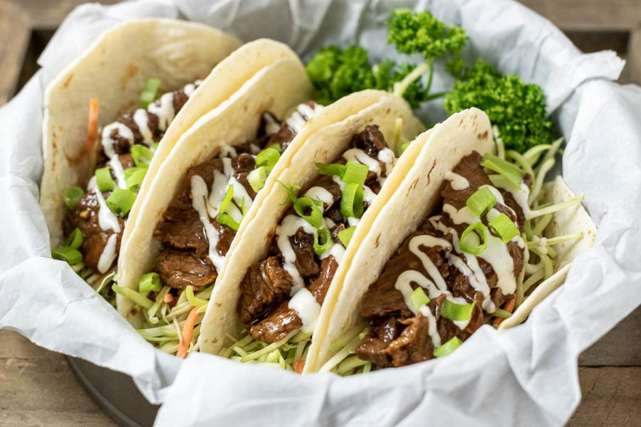 four Korean BBQ Tacos in a paper lined basket with parsley