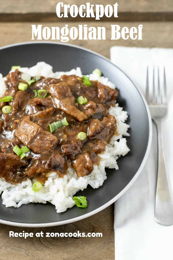 a fork and a plate filled with crockpot mongolian beef