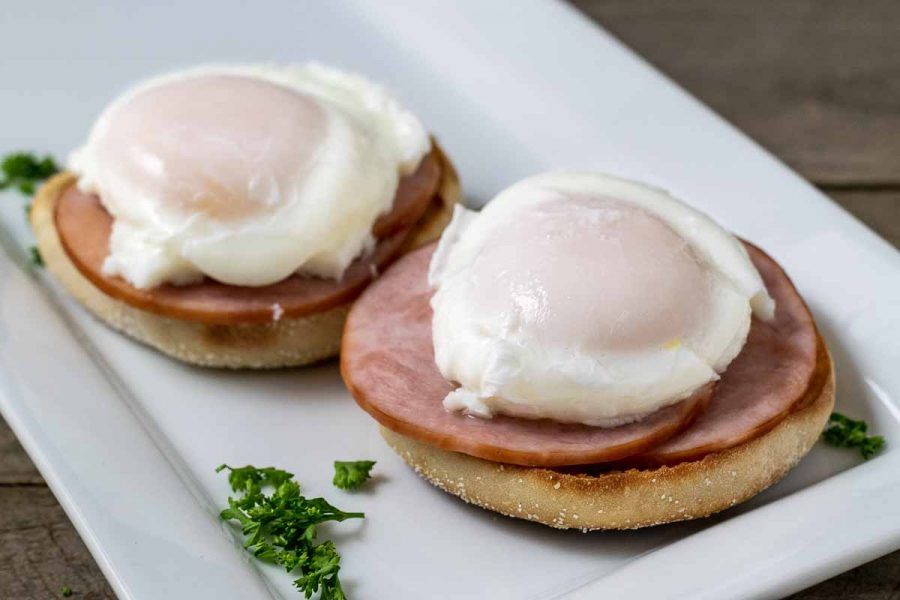 english muffin halves topped with canadian bacon and poached eggs on a platter