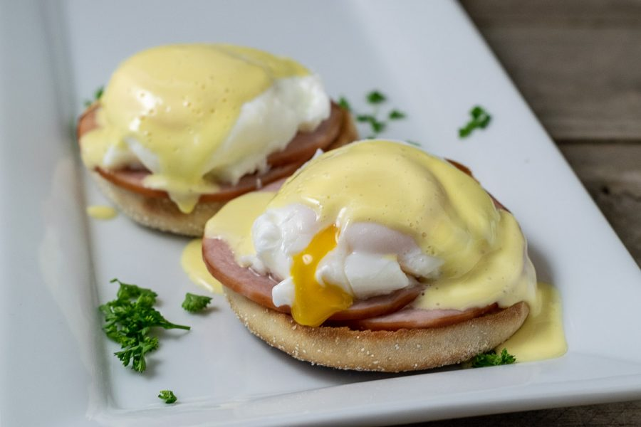 two Easy Eggs Benedict on a platter with some parsley